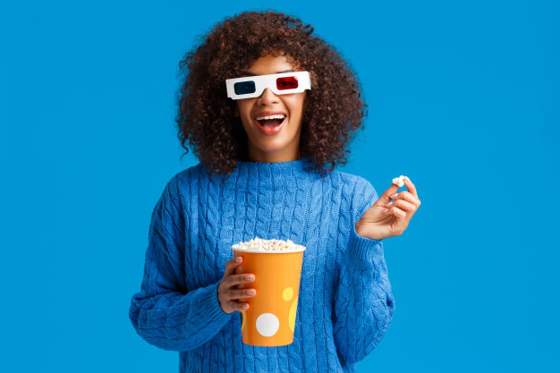 Leisure, lifestyle and modern people concept. carefree relaxed and joyful, smiling african american woman with afro hairstyle, eating popcorn in cinema, wear 3d glasses and smiling watching movie
