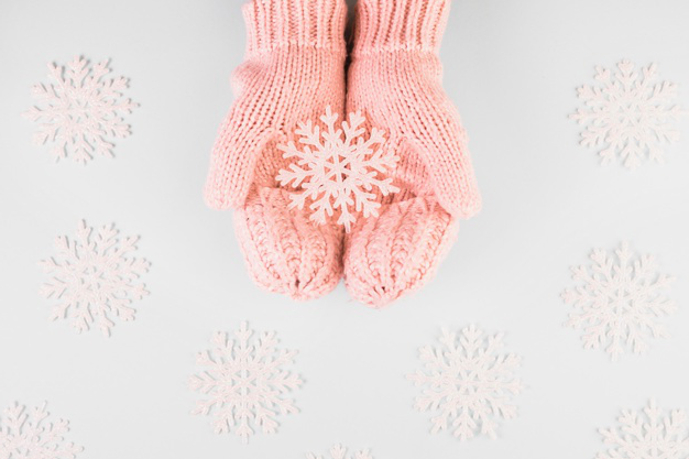 Human hands in mittens with paper snowflake