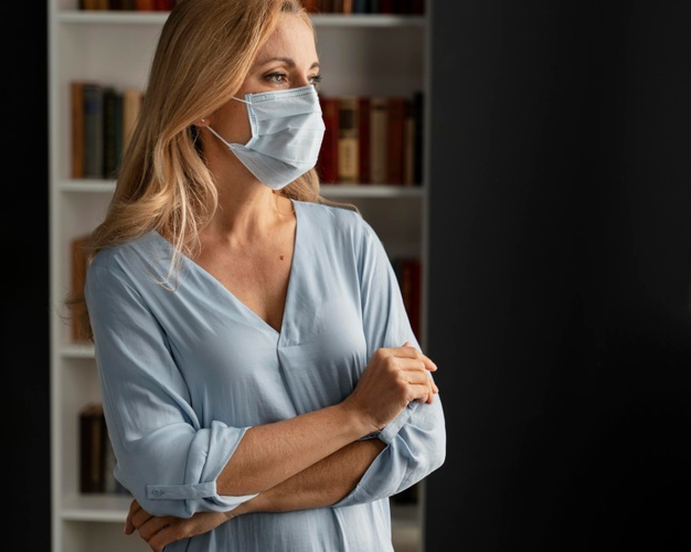 Mid shot worried woman counselor with face mask in office