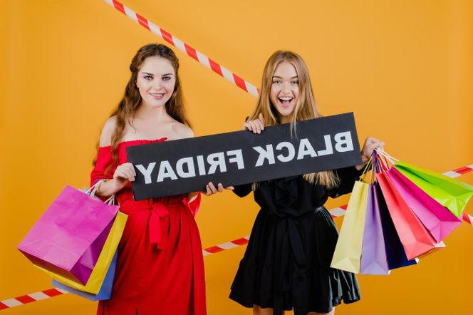 Two smiling pretty girls have black friday sign with colorful shopping bags and signal tape isolated over yellow