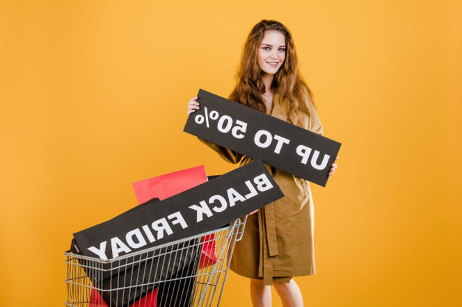 Young woman in trench coat with black friday 50% sign and colorful shopping bags in cart isolated over yellow